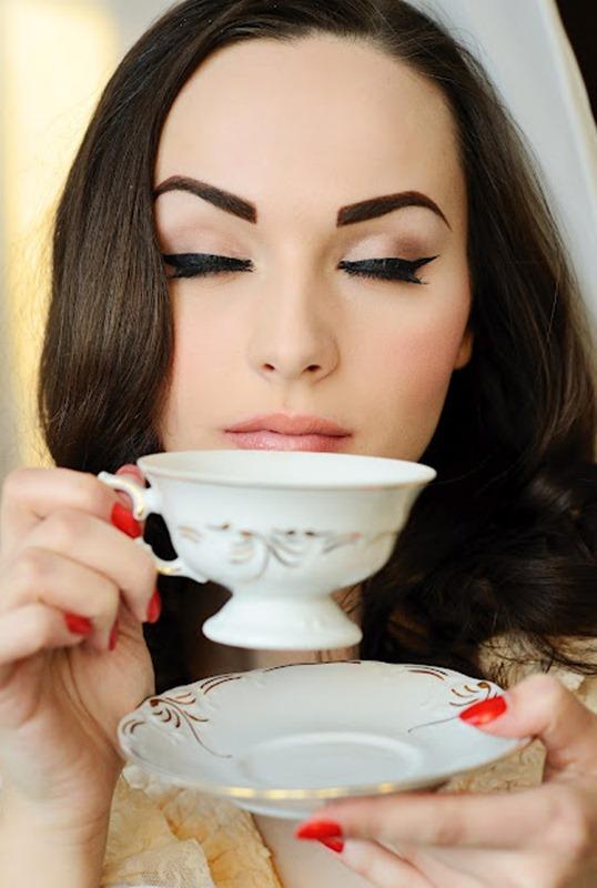 Девушка с красивым макияжем пьет чай