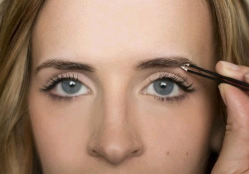 Девушка с голубыми глазами выщипывает брови
