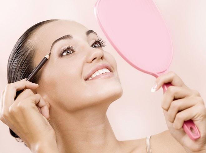 Девушка смотрится в зеркало и делает макияж