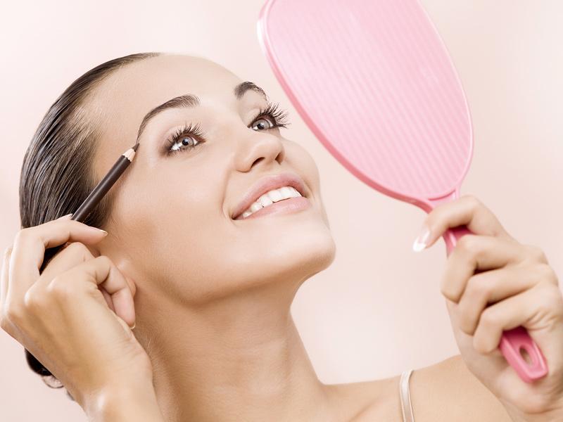Девушка делает макияж, глядя в розовое зеркало