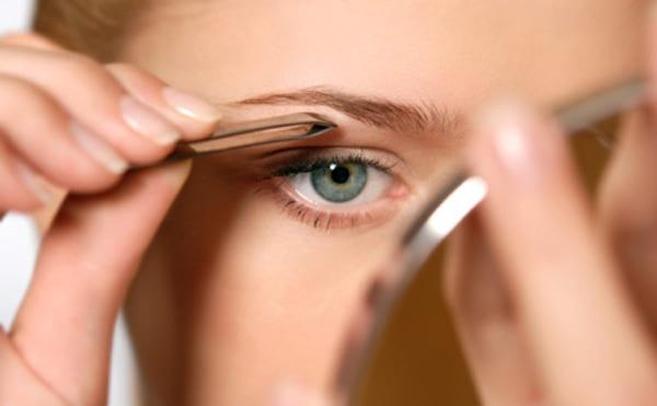 Девушка оформляет лицо с помощью щипчиков и зеркала