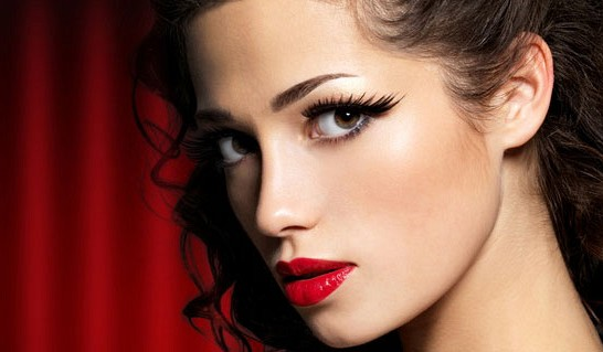 Девушка с вечерним макияжем на фоне красного занавеса
