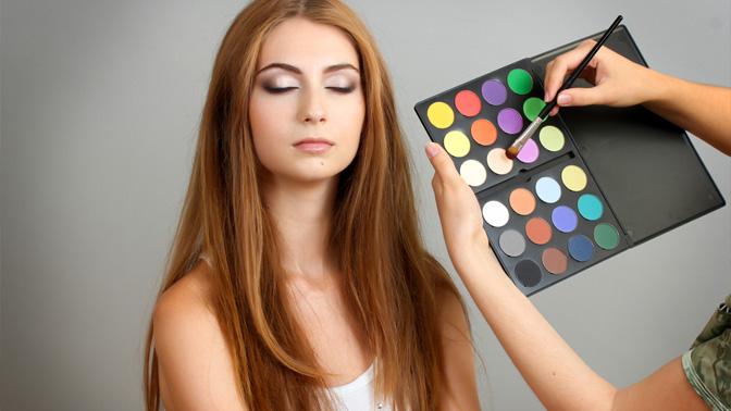 Девушку красят разноцветными тенями