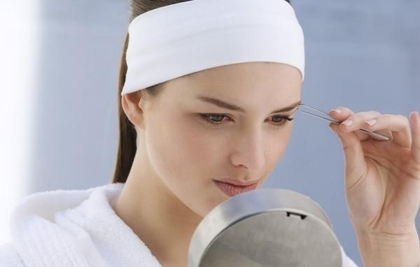 Девушка в белой повязке корректирует брови