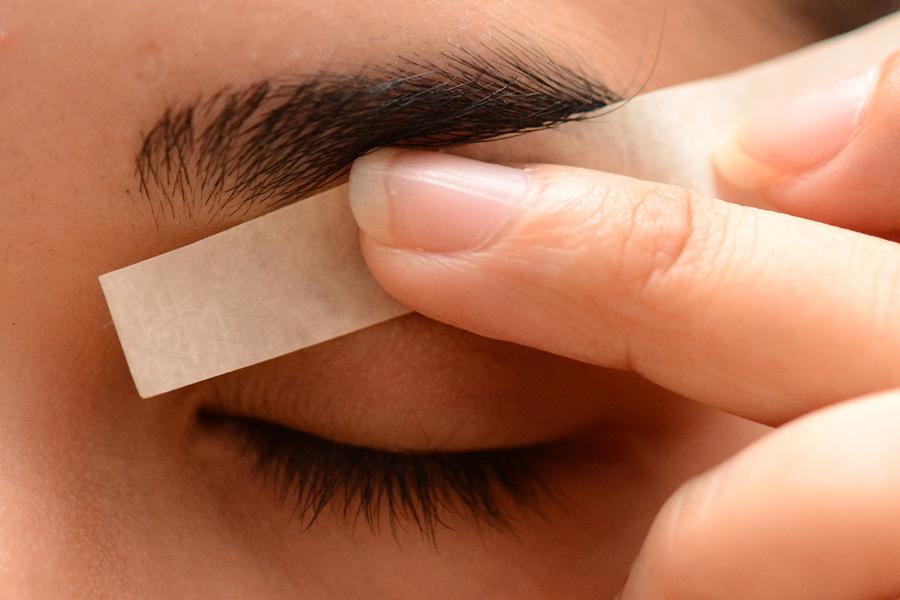 Процедура удаления волос под бровями с помощью воска и полоски бумаги
